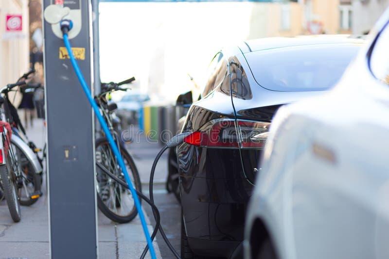 Aufladendes modernes Elektroauto auf der Straße als Zukunft der Automobilindustrie lizenzfreie stockfotografie