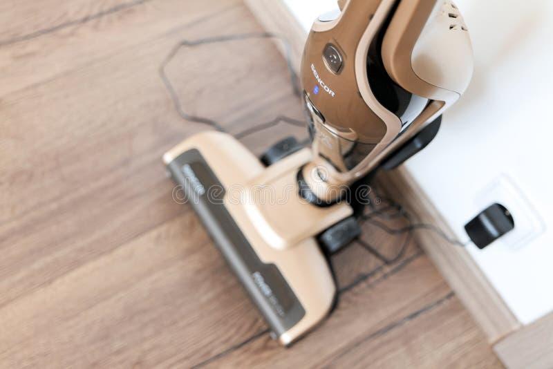 Aufladung den braunen tragbaren drahtlosen Sencor-Staubsauger auf einem Bretterboden für das Säubern eines Haushalts lizenzfreie stockfotografie