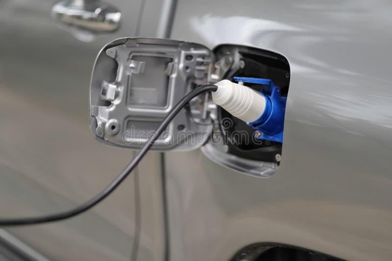 Aufladung ein Elektroauto mit der Stromkabelversorgung angeschlossen stockbild