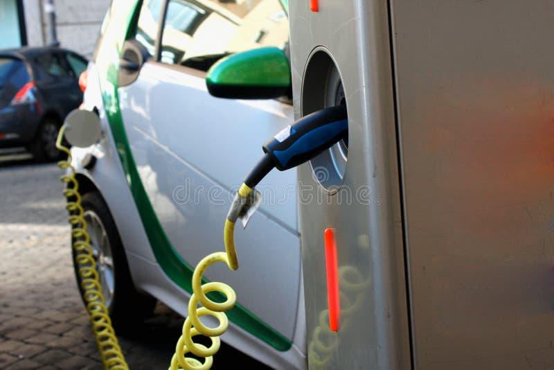 Aufladung ein Elektroauto mit der Stromkabelversorgung angeschlossen stockfotografie