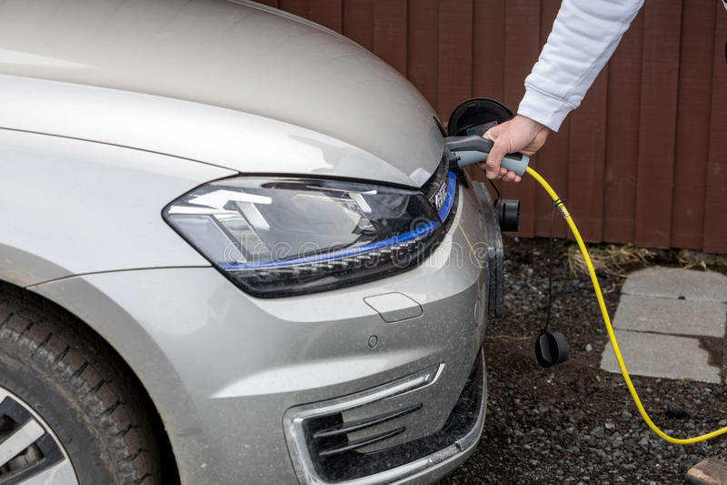 Aufladung ein Elektroauto mit der Stromkabelversorgung angeschlossen stockfotos