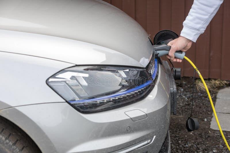 Aufladung ein Elektroauto mit der Stromkabelversorgung angeschlossen lizenzfreies stockbild