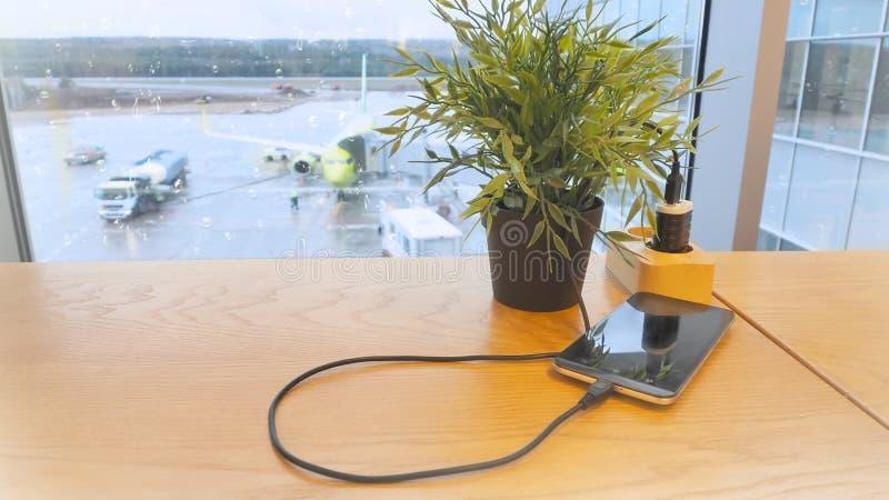 Aufladung einen Handy gegen einen Hintergrund der Brennstoffaufnahme eines Flugzeuges stockbild