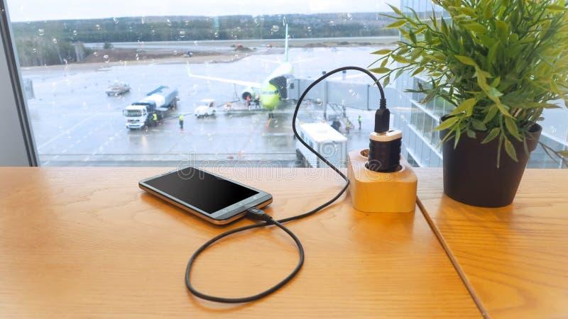 Aufladung einen Handy gegen einen Hintergrund der Brennstoffaufnahme eines Flugzeuges lizenzfreies stockfoto