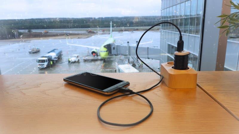 Aufladung einen Handy gegen einen Hintergrund der Brennstoffaufnahme eines Flugzeuges stockfoto