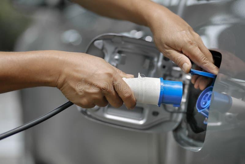 Aufladung eines Elektroautos mit der Stromkabelversorgung lizenzfreie stockfotografie