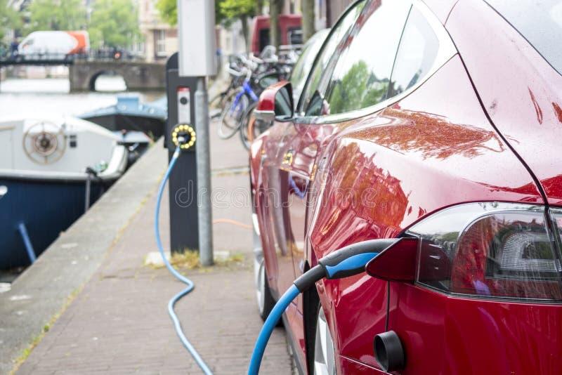 Aufladung eines roten Elektroautos stockfotos