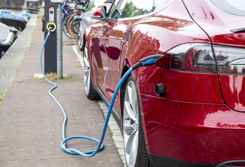 Aufladung eines roten Elektroautos lizenzfreie stockfotografie