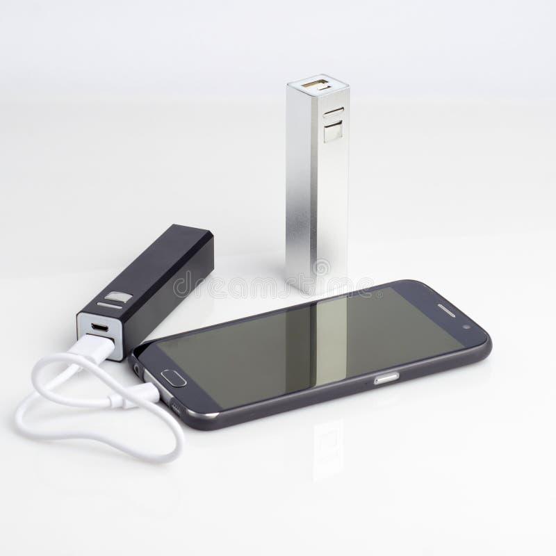 Aufladung eines Smartphone vom powerbank auf Weiß stockfotografie