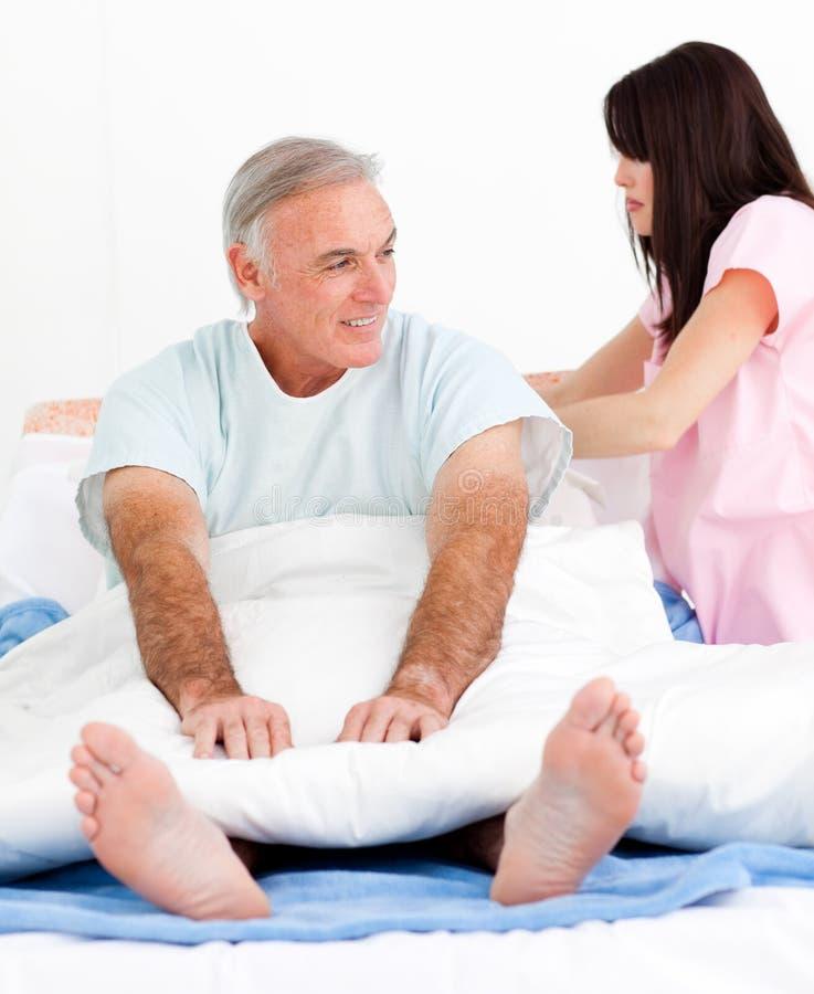 Aufmerksam Bett ihres Patienten der Krankenschwester Festlegung lizenzfreie stockfotografie