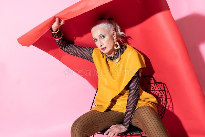 Aufmerksame ältere Frau, die auf Kamera im Studio aufwirft lizenzfreie stockbilder