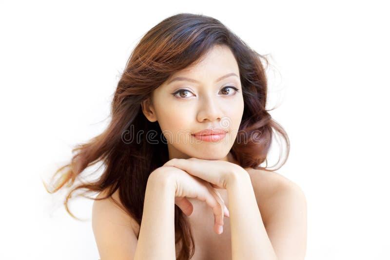 Aufmerksame asiatische Schönheit, die mit dem Kinn auf Händen wartet stockfotos