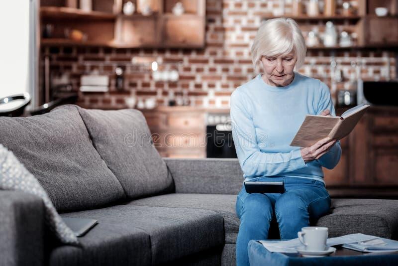 Aufmerksame blonde weibliche schauende Summenstelle lizenzfreie stockfotografie