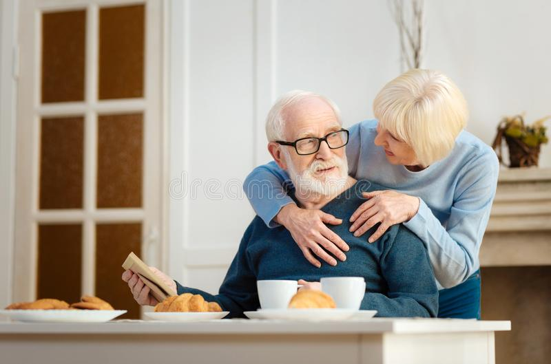 Aufmerksamer bärtiger Pensionär wendend Haupt an seine Frau stockfotos