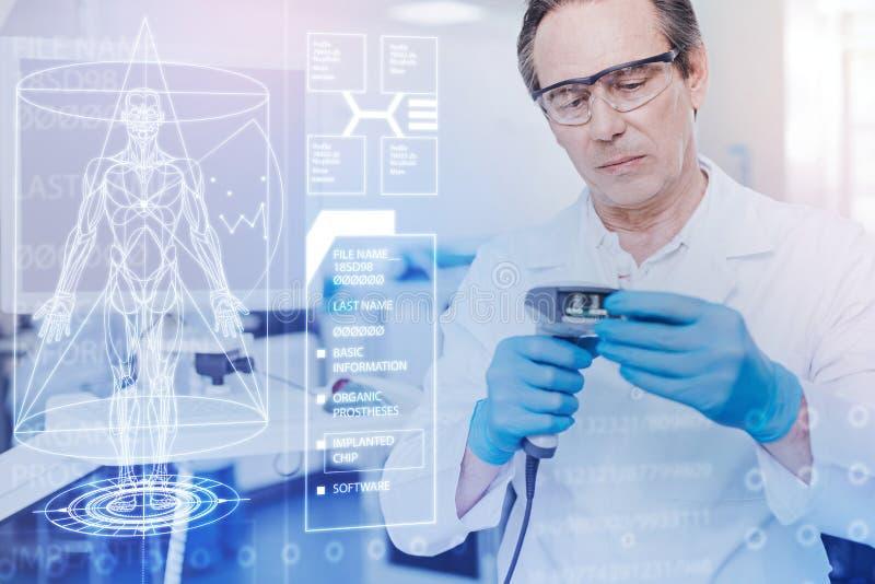 Aufmerksamer Doktor, der beim Arbeiten mit neuen Werkzeugen ernst schaut lizenzfreies stockfoto