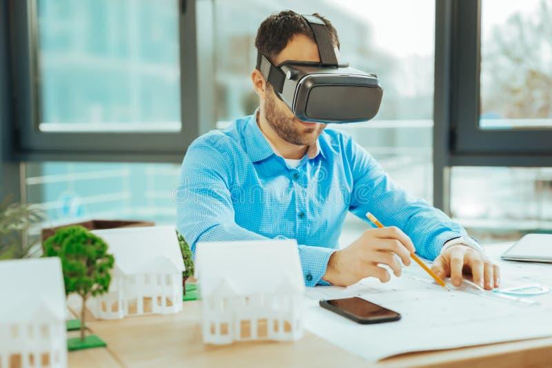 Aufmerksamer lächelnder Ingenieur beim Arbeiten mit Gläsern der virtuellen Realität stockfotografie