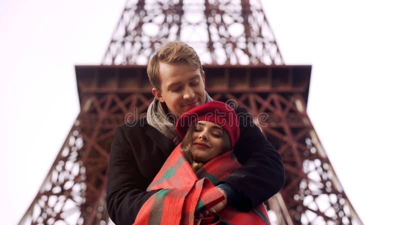 Aufmerksamer Mann, der seine gefrorene geliebte Dame in der Decke, Freiluftdatum in Paris einwickelt lizenzfreies stockbild