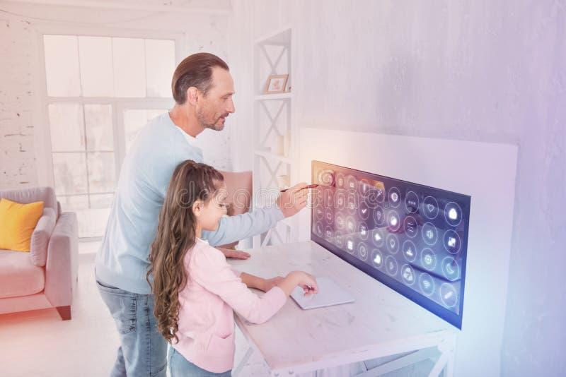 Aufmerksamer Programmierer, der den Schirm bei der Stellung nahe seiner Tochter betrachtet stockfotos