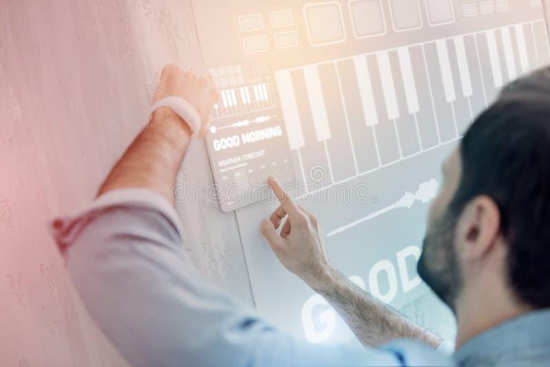 Aufmerksamer Programmierer, der in einem intelligenten Haus arbeitet und konzentriert schaut lizenzfreies stockbild