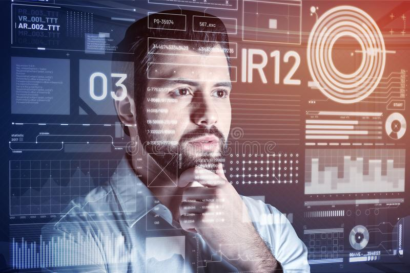 Aufmerksamer Programmierer, der seinen schwarzen Bart und Denken berührt lizenzfreie stockbilder