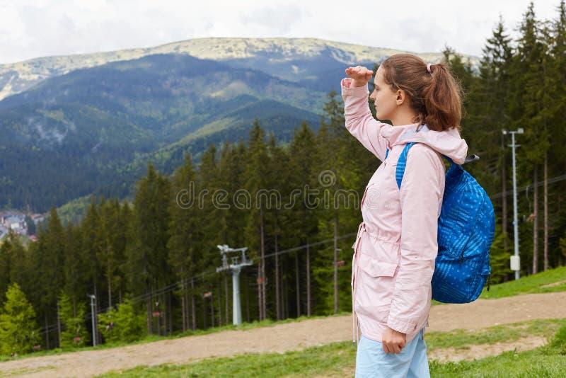Aufmerksamer starker Reisender, der, Arm anhebend direkt schaut und bedecken Augen mit der Hand und schützen sich vor Sonnenstrah lizenzfreie stockfotografie