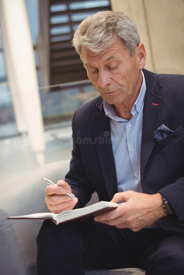 Aufmerksames Geschäftsmannschreiben im Organisator stockbild
