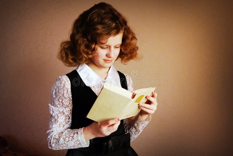 Aufmerksames Mädchenlesebuch im Geschäft kleidet auf braunem backgro stockbilder