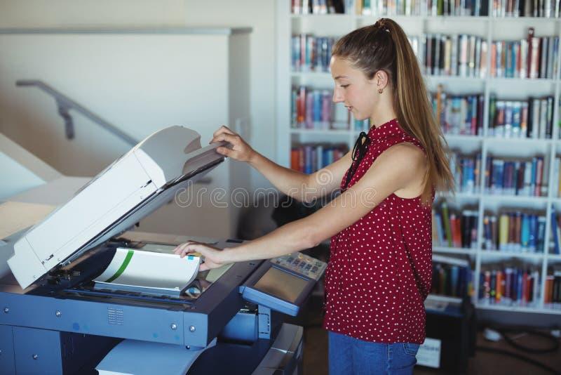 Aufmerksames Schulmädchen, das Xerox-Fotokopierer in der Bibliothek verwendet stockfoto