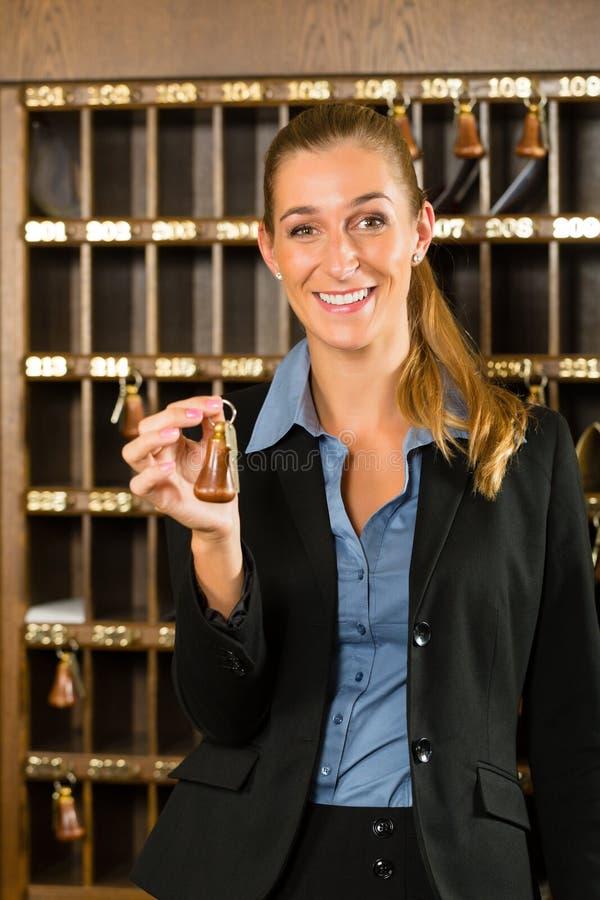Aufnahme des Hotels - Frau, die in der Hand Schlüssel hält stockfotografie