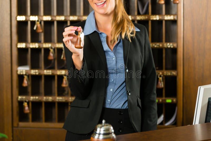 Aufnahme des Hotels - Frau, die in der Hand Taste anhält lizenzfreie stockbilder