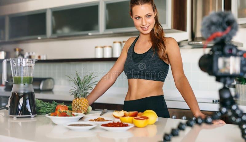 Aufnahmeinhalt der jungen Frau für ihr Blog in der Küche lizenzfreie stockfotografie