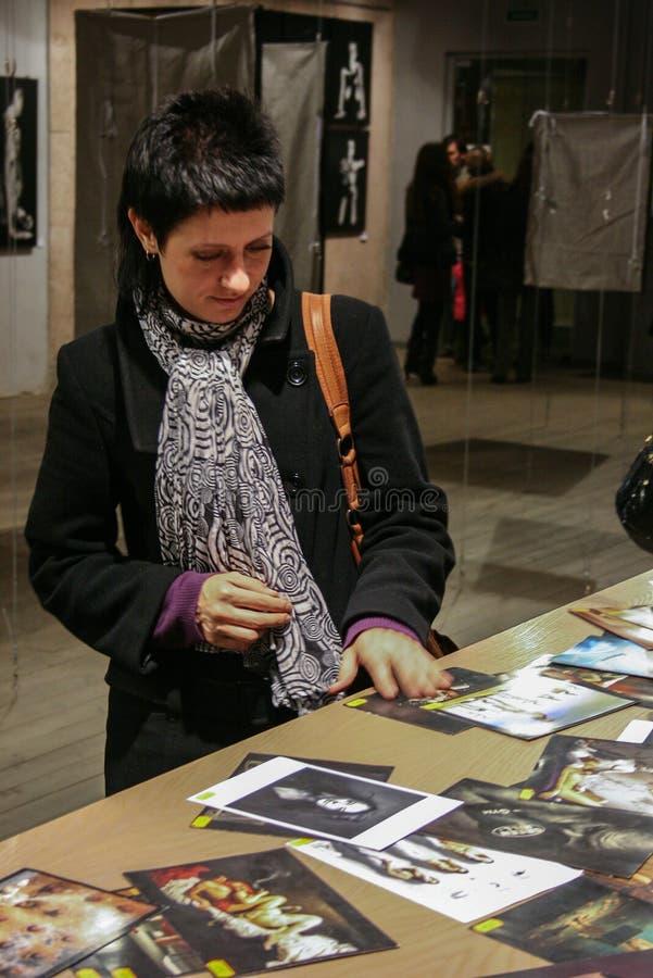 Aufpassende Bücher einer jungen Frau auf Hintergrund von Fotografie Innenraum des Buchladens stockfotografie