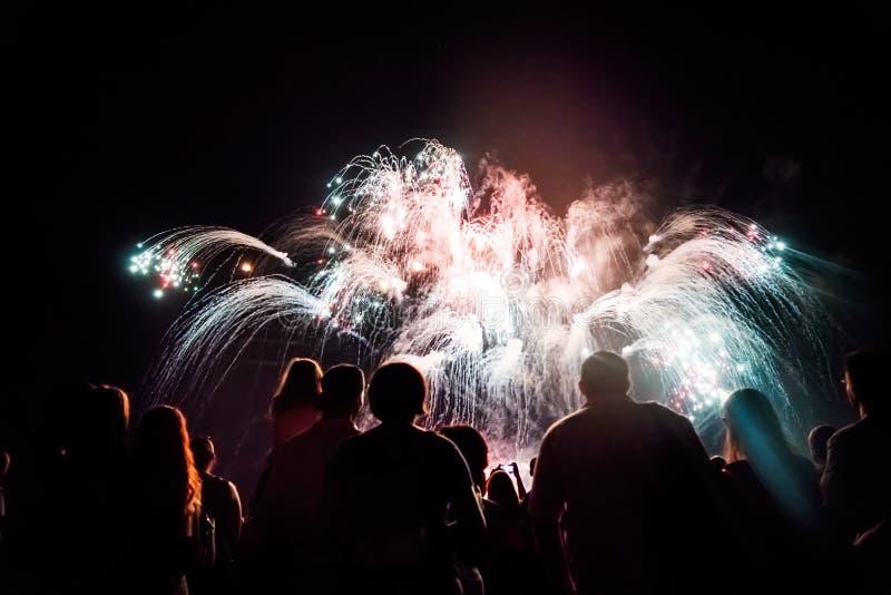 Aufpassende Feuerwerke der Menge und Feiern Sylvesterabend lizenzfreie stockfotografie