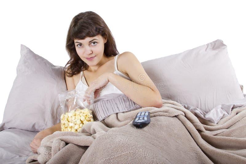 Aufpassende Filme im Bett stockfoto