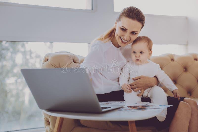 Aufpassende Karikaturen der herzensguten jungen Mutter auf Laptop mit ihrem Baby stockbild