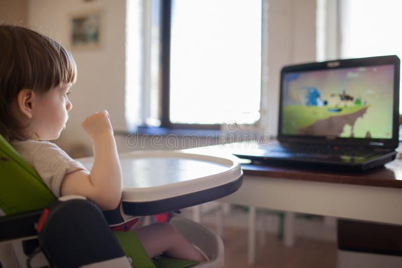 Aufpassende Karikaturen eines kleinen blonden Jungen auf dem Laptop beim Sitzen auf Kind-` s Stuhl stockbild