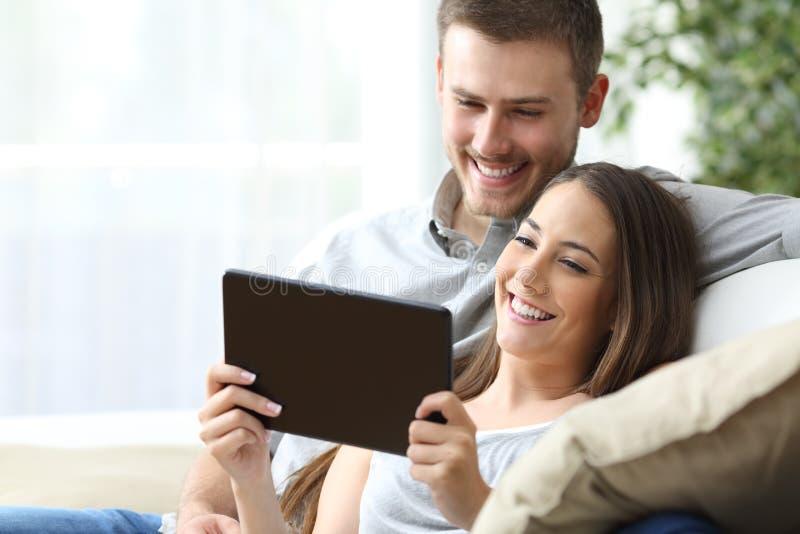 Aufpassende Medien der Paare in einer Tablette stockbilder