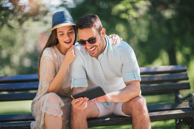 Aufpassende Medien des glücklichen Paars in einer digitalen Tablette lizenzfreies stockbild