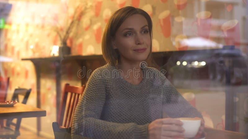 Aufpassende Passanten der durchdachten Frau durch Fenster ihres Lieblingskaffeehauses stockfoto