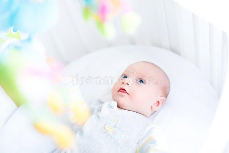 Aufpassende Spielwaren des netten neugeborenen Babys in seiner weißen Krippe stockbild