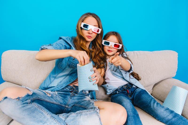 Aufpassender Film in den Gläsern 3D der glücklichen Mutter und ihrer Tochter in der Jeanskleidung auf Couch auf blauem Hintergrun lizenzfreies stockbild