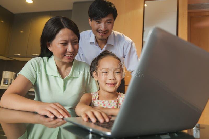 Aufpassender Film der Familie auf dem Laptop stockbild