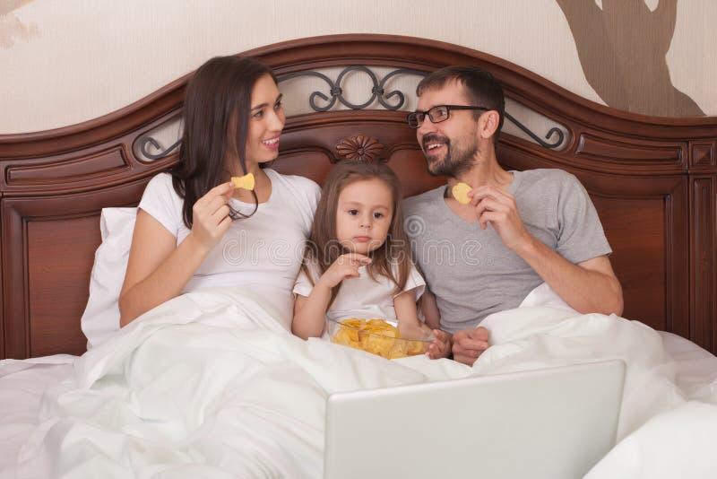Aufpassender Film der glücklichen Familie im Bett und in den essen Chips stockbilder