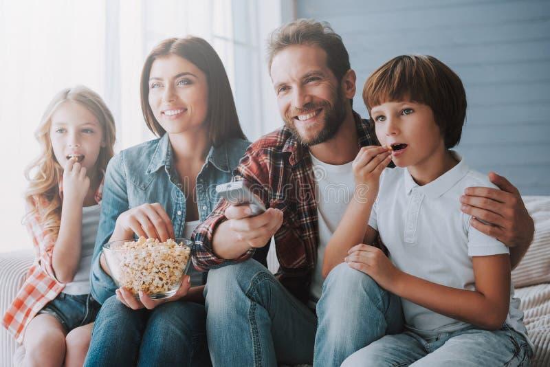 Aufpassender Film der glücklichen Familie zusammen und Popcorn essend während zu Hause stockfotografie