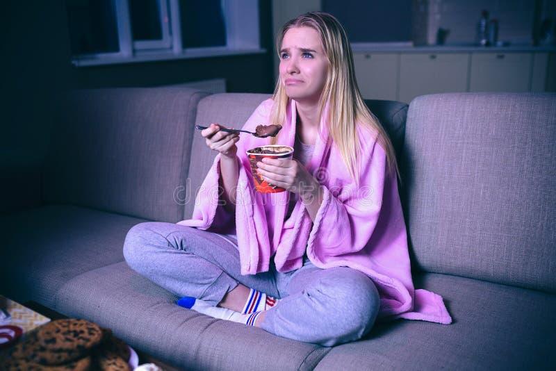 Aufpassender Film der jungen Frau nachts Sitzen mit den Händen gekreuzt und Essen von Bonbons Pl?tzchen auf Tabelle Emotionales g lizenzfreie stockfotos