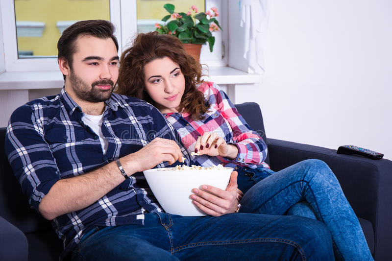Aufpassender Film der jungen Paare auf Fernsehen und zu Hause essen Popcorn lizenzfreie stockbilder