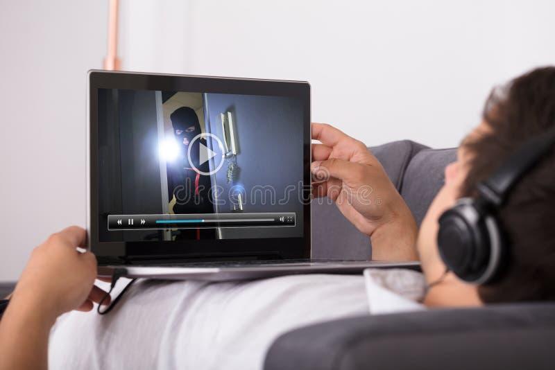 Aufpassender Film des Mannes auf Laptop stockfotografie