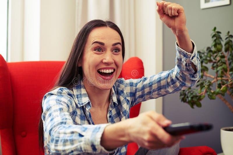 Aufpassender Fußball der emotionalen Frau im Fernsehen stockfotografie