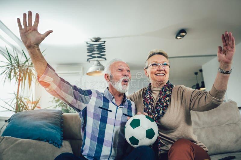 Aufpassender Fußball der glücklichen älteren Paare im Fernsehen lizenzfreie stockfotografie