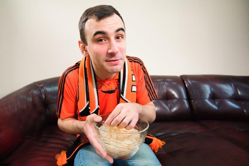 Aufpassender Fußball des Mannes und essen Chips, Fußballfan stockbilder
